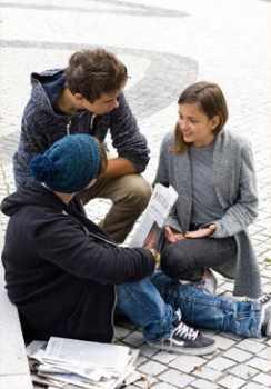 Drei Jugendliche diskutieren auf einem Platz über einen Zeitungsartikel